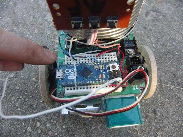 Here is the Arduino and circuitry mounted on a Boe-Bot chassis. I'm pointing to the calibration wire, which is currently connected.
